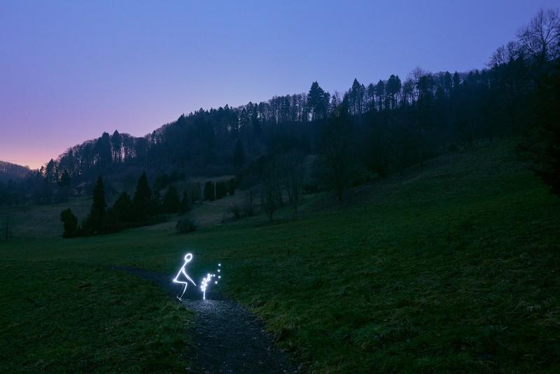 Arboretum, Aubonne en Suisse. Un personnage de lumière plante un arbre.